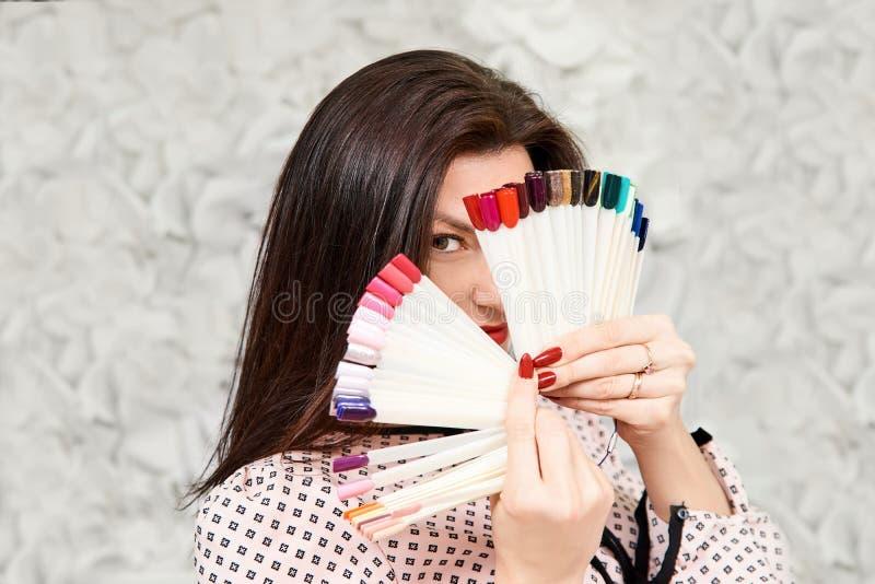 Una muchacha con una manicura hermosa, sosteniendo las muestras de la manicura, cubriendo su cara Morena imagen de archivo