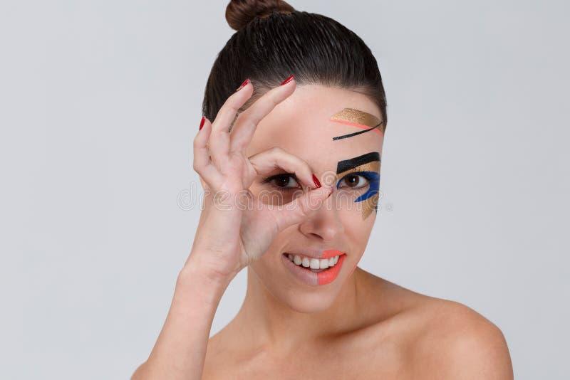 Una muchacha con maquillaje creativo que sonríe y que mira a través de su índice y pulgar en un fondo gris fotografía de archivo