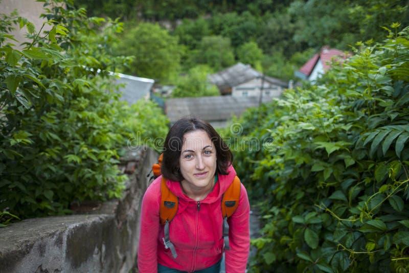 Una muchacha con una mochila sube las escaleras foto de archivo