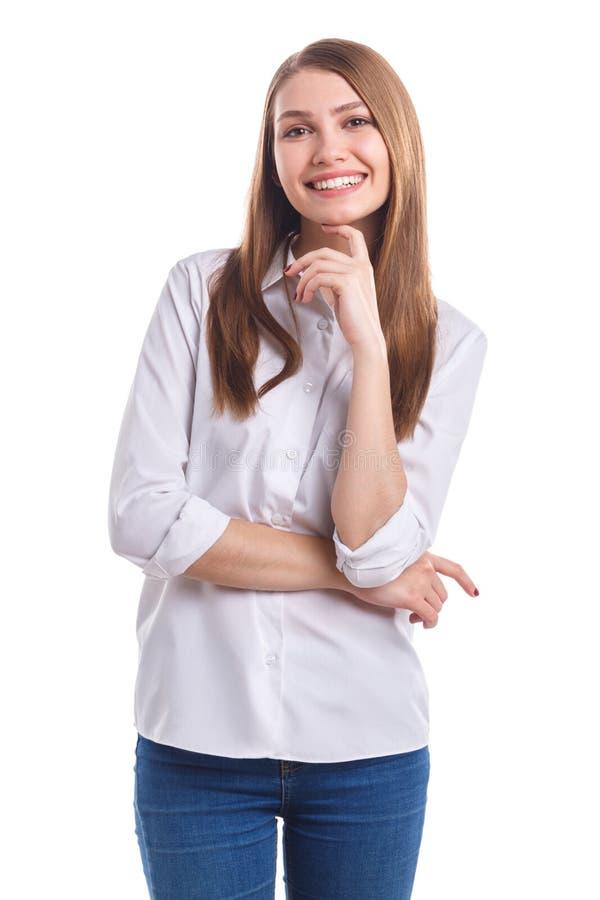 Una muchacha con una sonrisa lleva a cabo su mano debajo de su barbilla contra un fondo aislado blanco fotos de archivo