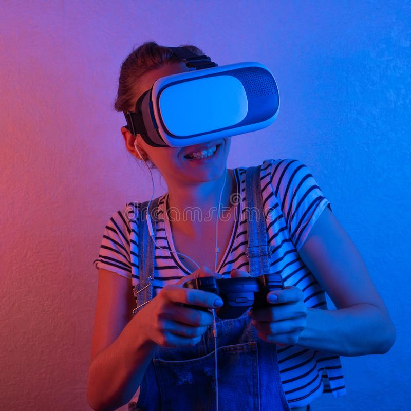 Una muchacha con un gamepad en vidrios del vr, jugando con la luz azul y roja El concepto de innovaci?n y del futuro imagenes de archivo
