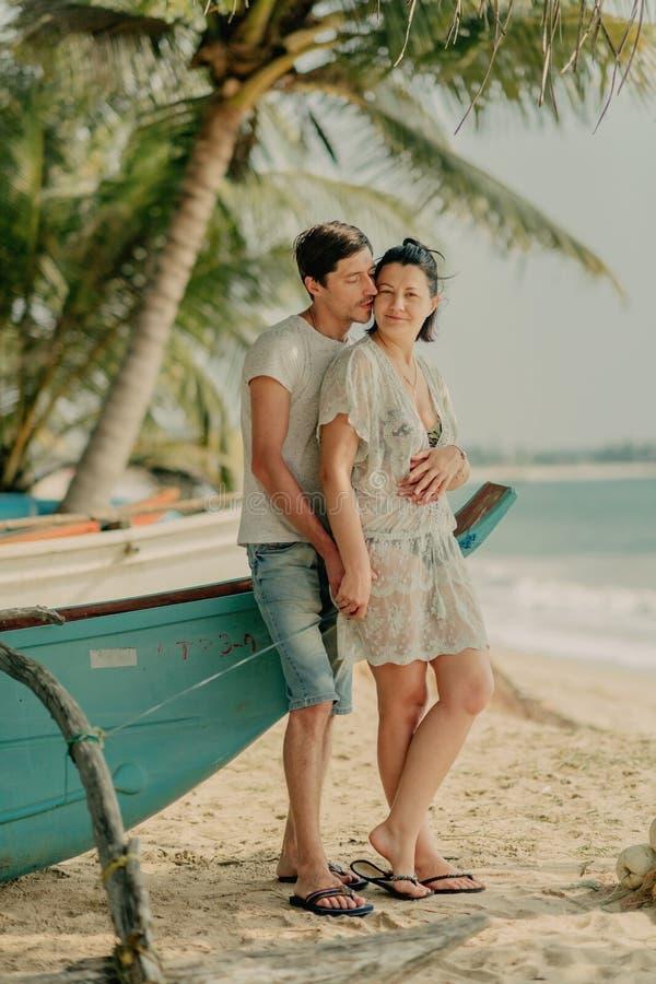Una muchacha con un hombre que sostiene un barco cerca del océano fotografía de archivo