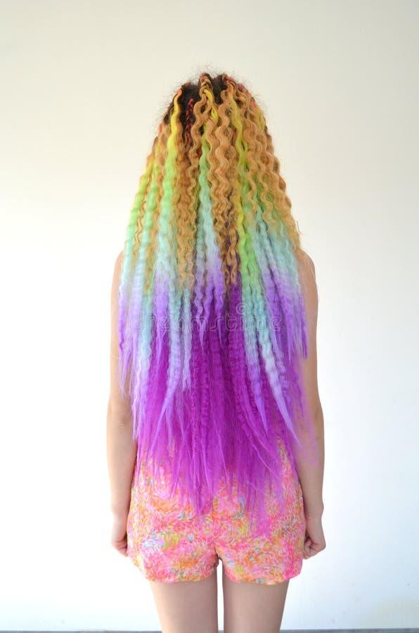 Una muchacha con un pelo ondulado largo pintado en colores del arco iris Kanekalon del pelo de la túnica foto de archivo