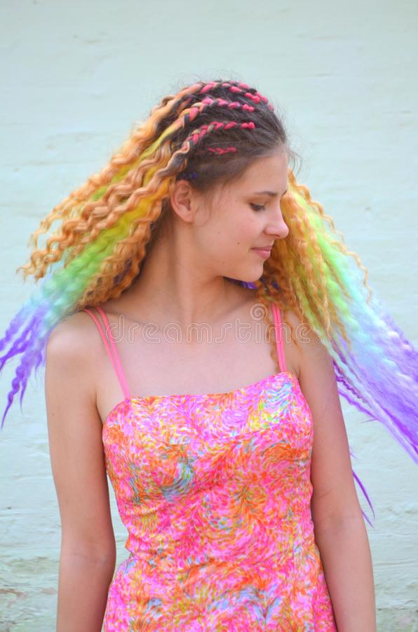 Una muchacha con un pelo ondulado largo pintado en colores del arco iris Kanekalon del pelo de la túnica fotos de archivo libres de regalías