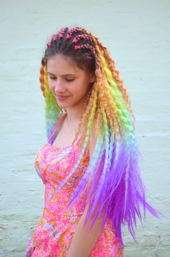 Una muchacha con un pelo ondulado largo pintado en colores del arco iris Kanekalon del pelo de la túnica imagen de archivo