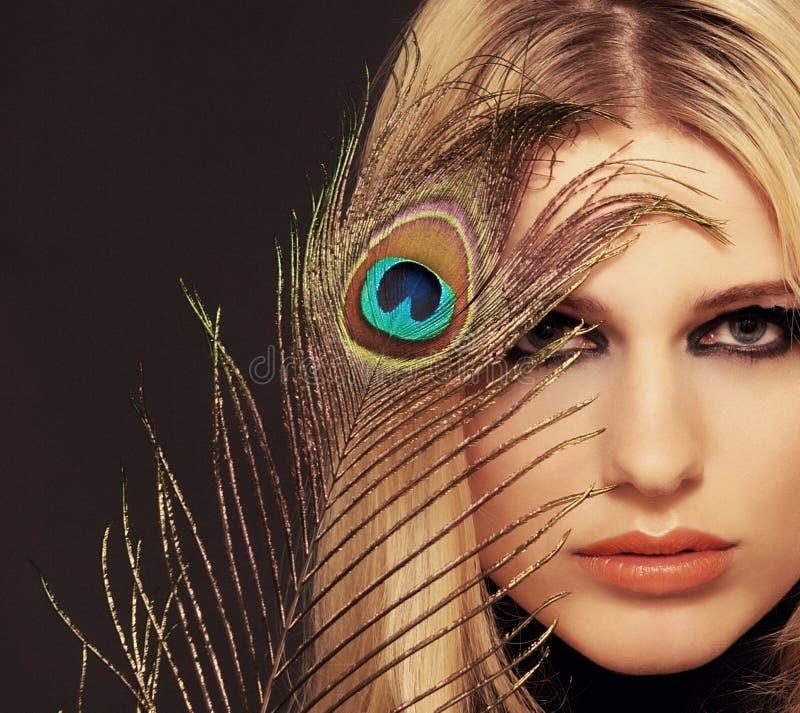 Una muchacha con una pluma. imagen de archivo libre de regalías