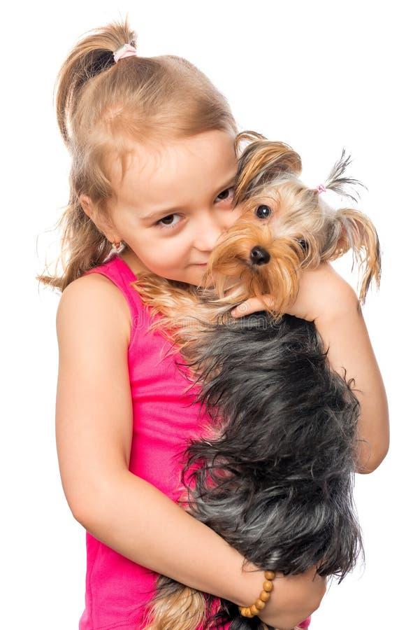 Una muchacha controles de 6 años un perro casero fotos de archivo