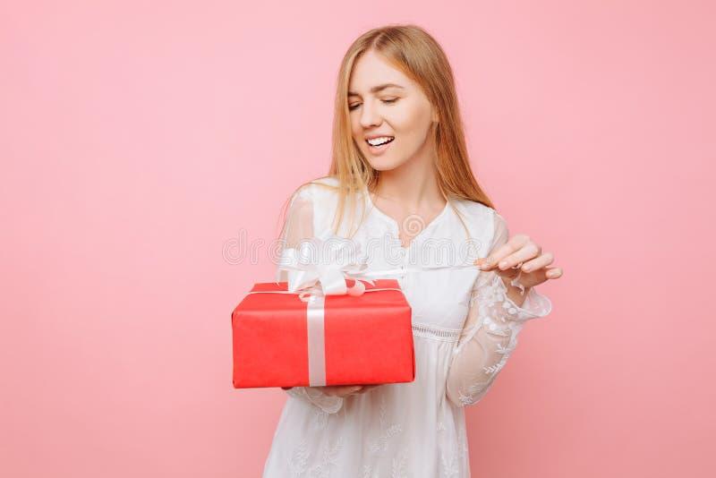 Una muchacha curiosa en un vestido blanco con una caja de regalo en su mano, quiere ver cuál está en la caja, en DA de una tarjet fotografía de archivo libre de regalías