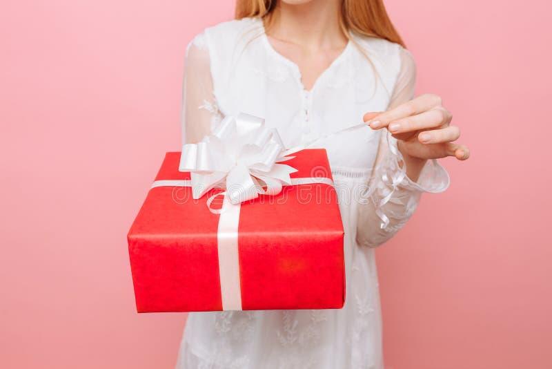Una muchacha curiosa en un vestido blanco con una caja de regalo en su mano, quiere ver cuál está en la caja, en DA de una tarjet fotos de archivo libres de regalías