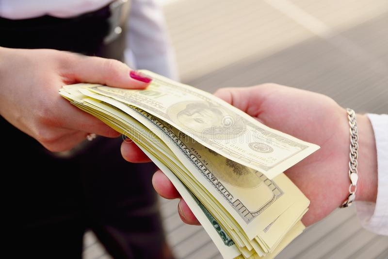 Una muchacha da a un hombre en las manos del dinero en el fondo del imagen de archivo