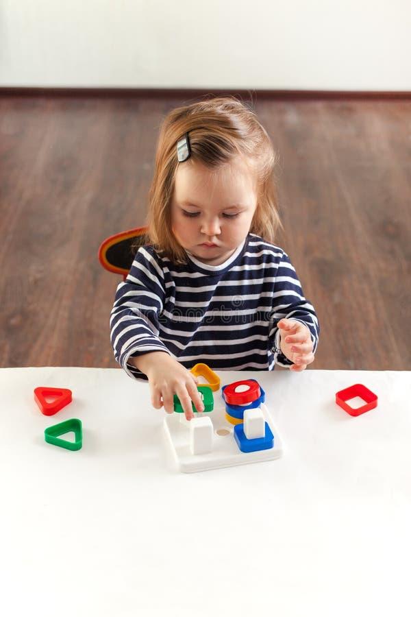 Una muchacha de 1,5 años con el pelo largo en un vestido rayado se sienta en la tabla y los juegos con convertirse juegan, una té fotografía de archivo libre de regalías