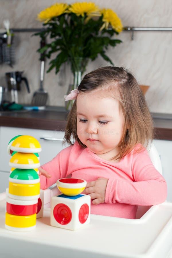 Una muchacha de 2 años con los juegos largos del pelo con una construcción del diseñador en casa, construye torres, disfruta en l fotos de archivo
