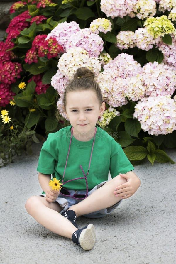 Una muchacha de cuatro años delante de varias plantas florecientes foto de archivo