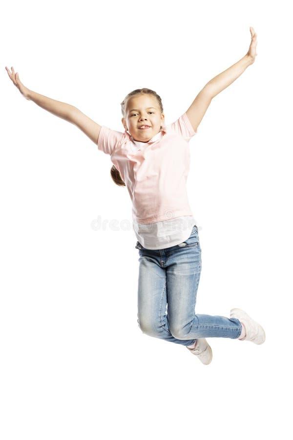 Una muchacha de la escuela-edad en un suéter rosado y vaqueros está saltando Aislado sobre el fondo blanco fotografía de archivo libre de regalías