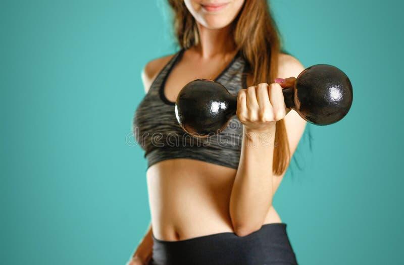 Una muchacha de los deportes que lleva a cabo pesa de gimnasia negra foto de archivo
