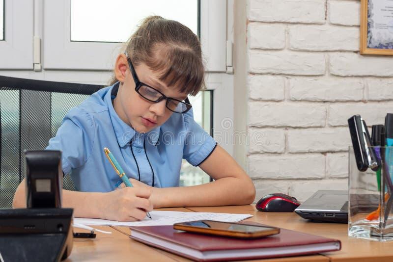 Una muchacha de ocho años en la tabla en la oficina escribe una pluma en un trozo de papel imagen de archivo libre de regalías