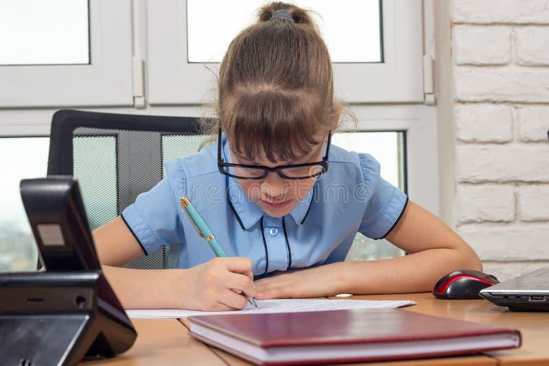 Una muchacha de ocho años escribe en un escritorio en un ajuste de la oficina fotografía de archivo libre de regalías