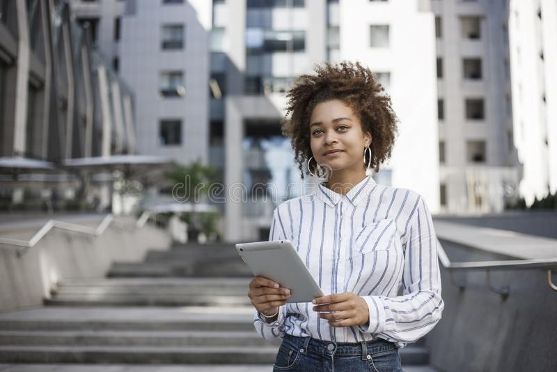 Una muchacha de piel morena se coloca en la calle cerca del centro de negocios Ella celebra la tableta y las sonrisas Edificio de fotografía de archivo