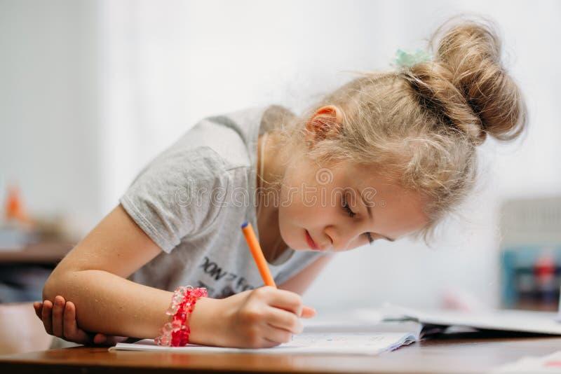 Una muchacha de siete años se sienta en casa en una tabla y escribe en un cuaderno, terminando una tarea de aprendizaje o repitie imagenes de archivo