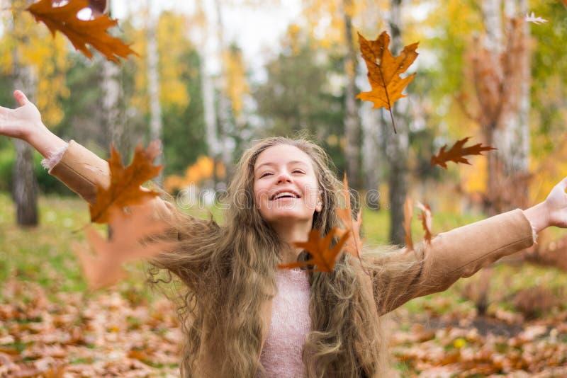 Una muchacha del adolescente en una capa ríe y lanza para arriba las hojas en otoño imagen de archivo