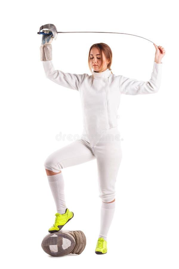 Una muchacha del cercador, en un uniforme de cercado, mirando abajo y sosteniendo una espada en sus brazos Aislado imagenes de archivo