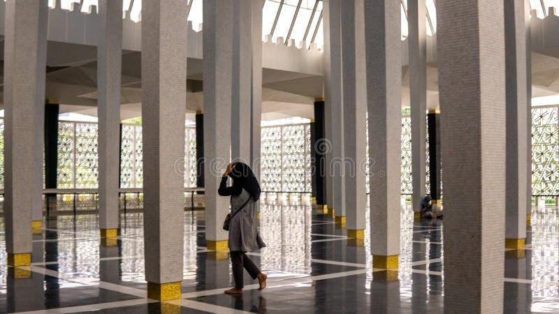 Una muchacha del hijab que camina en la mezquita o el Masjid nacional Negara en Kuala Lumpur La mezquita tiene interior e islámic fotos de archivo libres de regalías