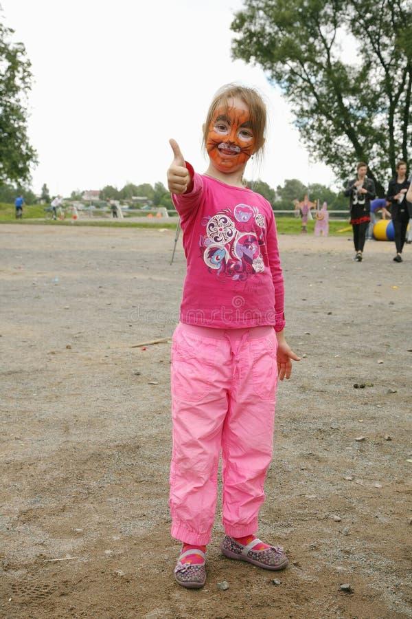 Una muchacha del niño con la cara pintada del leopardo que juega en el parque municipal del patio foto de archivo