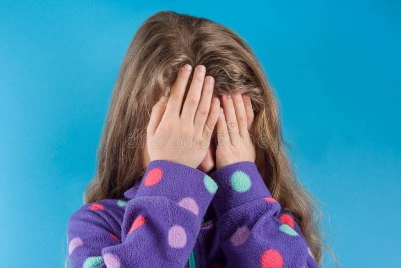 Una muchacha del niño cubrió su cara con las manos, en un fondo azul del estudio imagenes de archivo