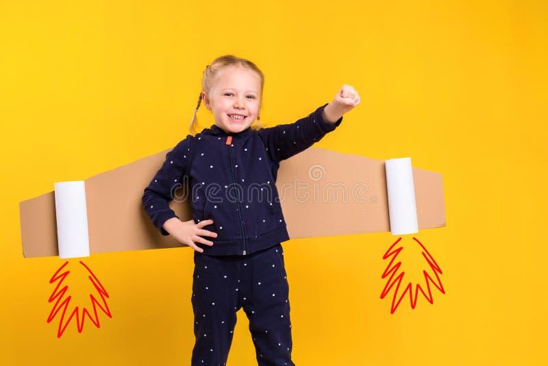 Una muchacha del pequeño niño está llevando las alas de vuelo hechas en casa de la cartulina, fingiendo ser piloto para un arte,  fotografía de archivo