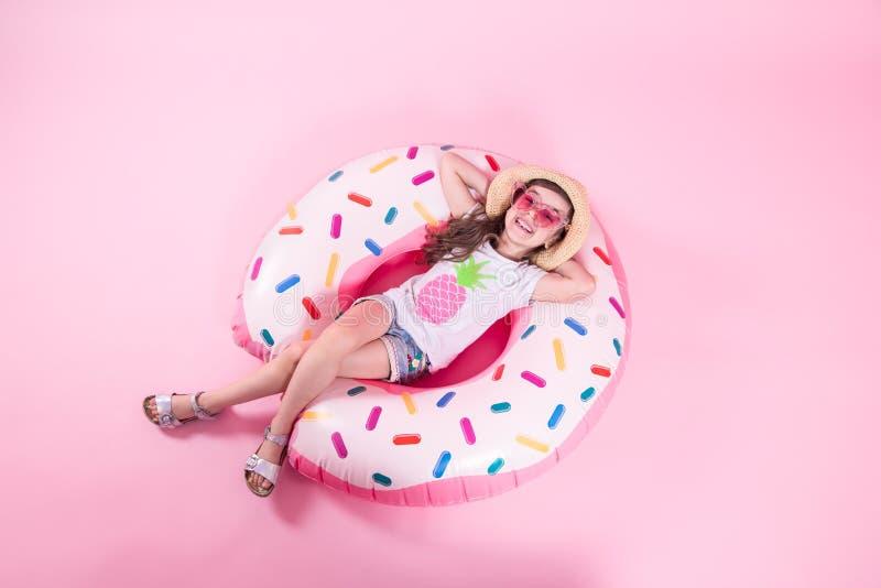 Una muchacha del peque?o ni?o que miente en un c?rculo inflable del bu?uelo Fondo rosado Visi?n superior Concepto del verano fotografía de archivo libre de regalías