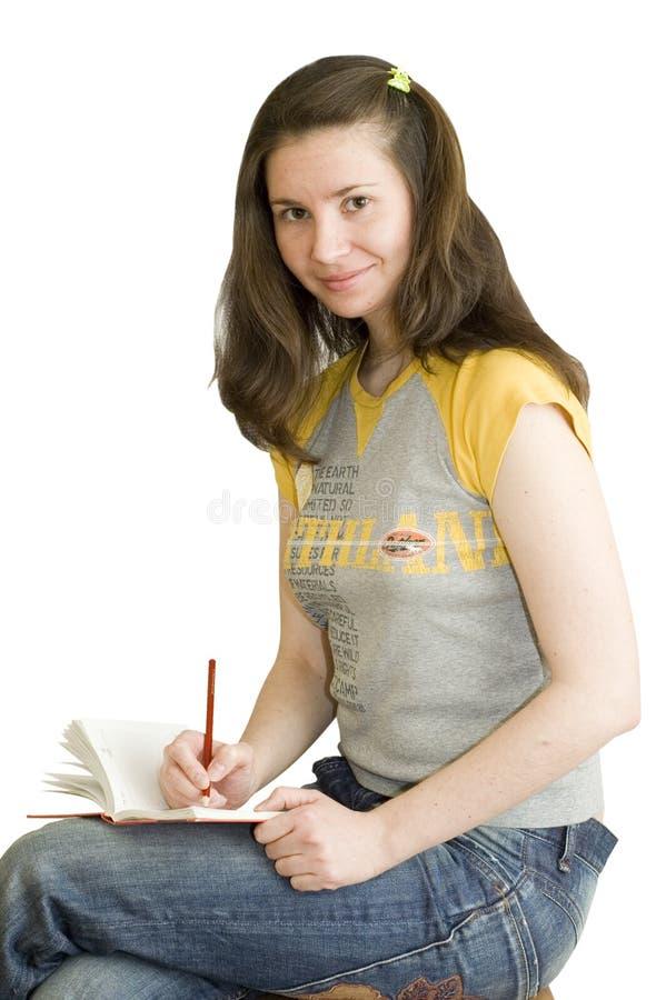 Una muchacha del programa de escritura con la pista de nota imagen de archivo