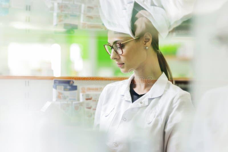 Una muchacha delgada apuesta con el pelo oscuro y los vidrios, llevando un guardapolvo médico, lee algo en la caja de la medicina fotos de archivo libres de regalías