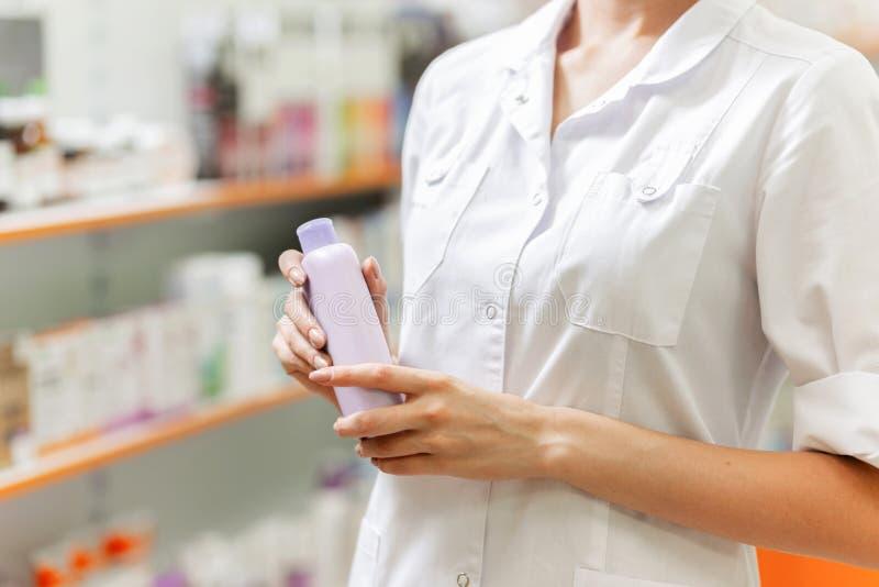 Una muchacha delgada joven, vestida en una capa blanca, está llevando a cabo un espray en sus manos en una nueva farmacia foto de archivo libre de regalías