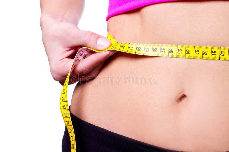 Una muchacha delgada que mide su cintura imagenes de archivo
