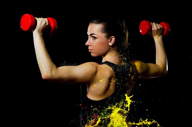 Una muchacha deportiva está haciendo un ejercicio en el cultivo de manos con pesas de gimnasia Se baña en pintura amarilla foto de archivo