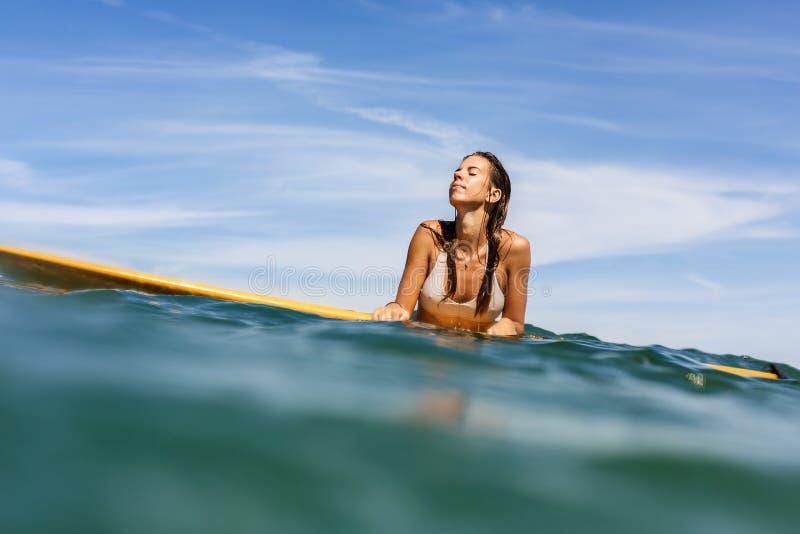 Una muchacha deportiva hermosa que practica surf en el océano fotografía de archivo