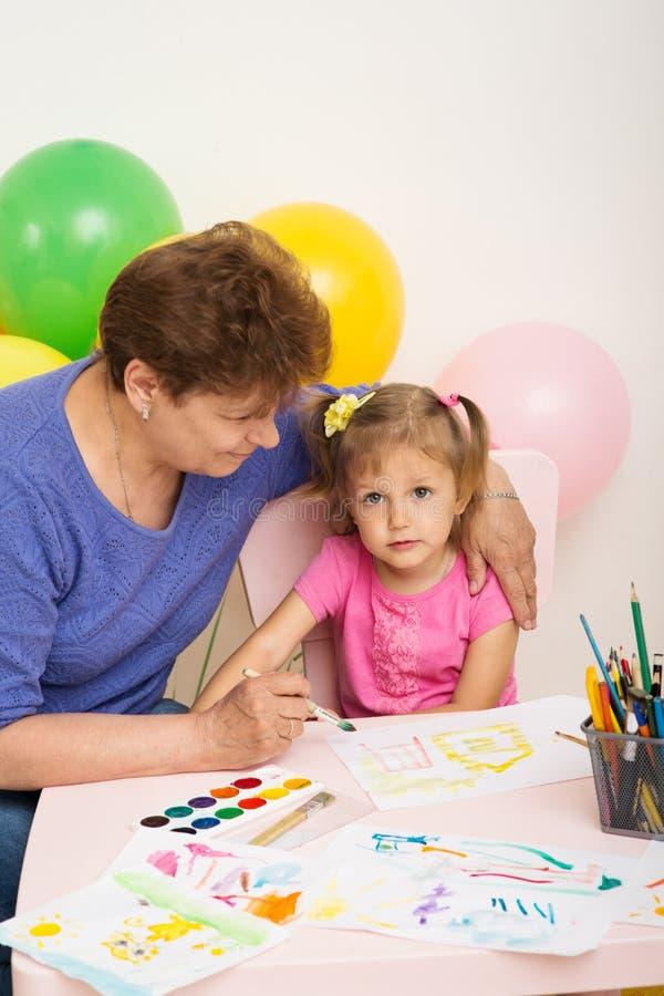 Una muchacha dibuja con su abuela fotografía de archivo libre de regalías