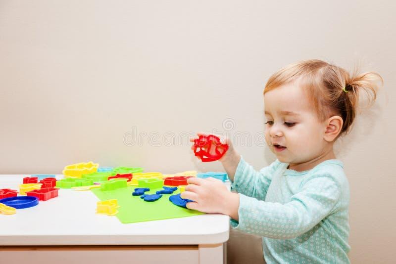 Una muchacha divertida del año que se divierte con el modelado de la pasta en la guardería imagenes de archivo