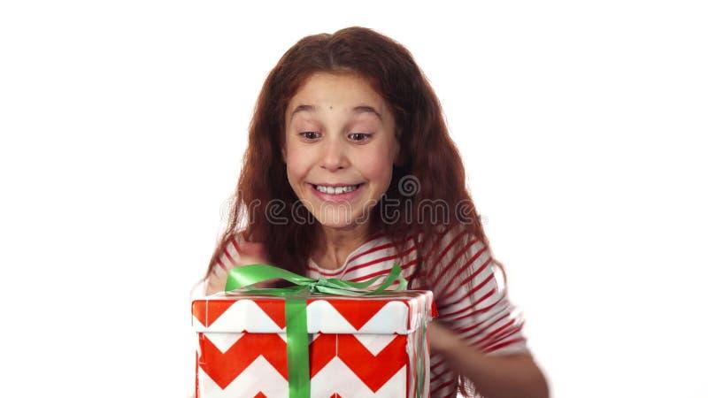 Una muchacha dulce la abre los ojos y recibe su regalo del Año Nuevo imágenes de archivo libres de regalías