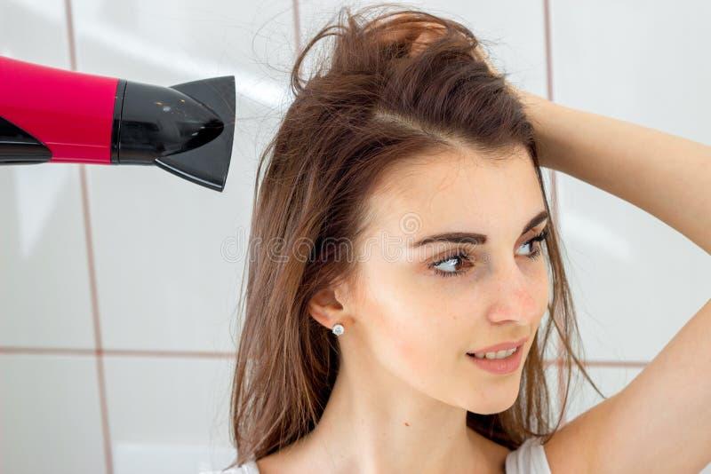 Una muchacha el cabello seco en el cuarto de baño fotos de archivo