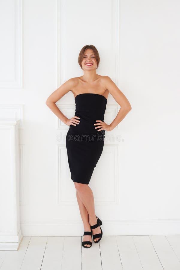 Una muchacha elegante con una sonrisa coqueta está presentando en un vestido negro fotografía de archivo libre de regalías