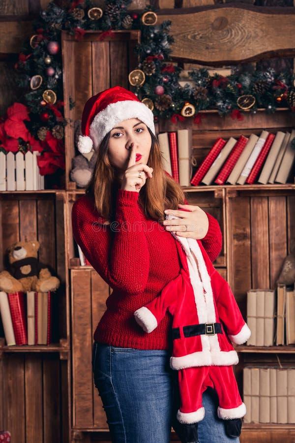 Una muchacha embarazada sostiene un traje de la Navidad para el bebé y muestra shhh fotografía de archivo