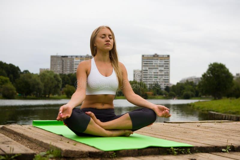 Una muchacha en una actitud del loto se sienta en un parque de la ciudad foto de archivo libre de regalías