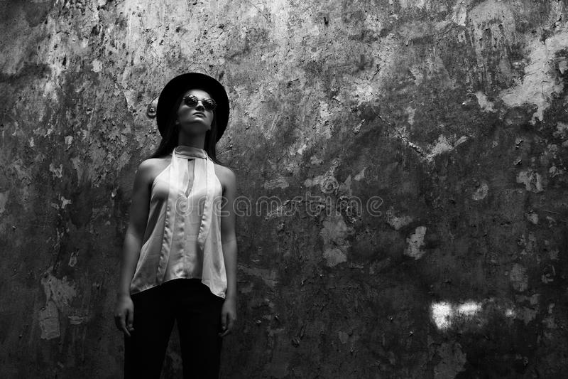 Una muchacha en una blusa blanca, con la vicia destruyó el edificio Helouin Foto blanco y negro de Pekín, China fotos de archivo