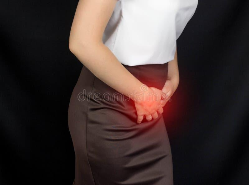 Una muchacha en una blusa del blanco se sostiene sobre la ingle del abdomen más bajo, sus daños del estómago, publicaciones mensu imágenes de archivo libres de regalías