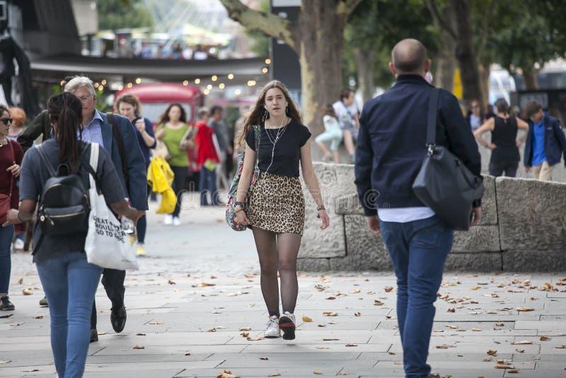 Una muchacha en una blusa negra y una falda corta del leopardo está caminando a lo largo del banco del sur fotos de archivo