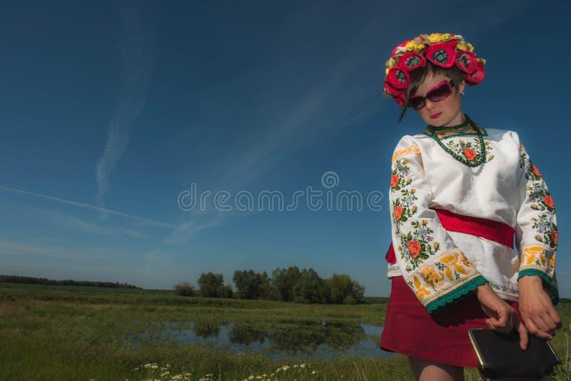 Una muchacha en bordado ucraniano con una guirnalda en su cabeza por el lago en un prado entre las flores imagen de archivo libre de regalías
