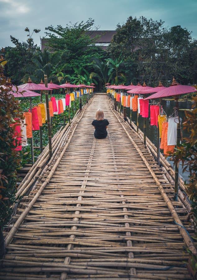 Una muchacha en una camiseta negra se está sentando con ella de nuevo a la cámara en una trayectoria de bambú adornada con los pa fotos de archivo libres de regalías