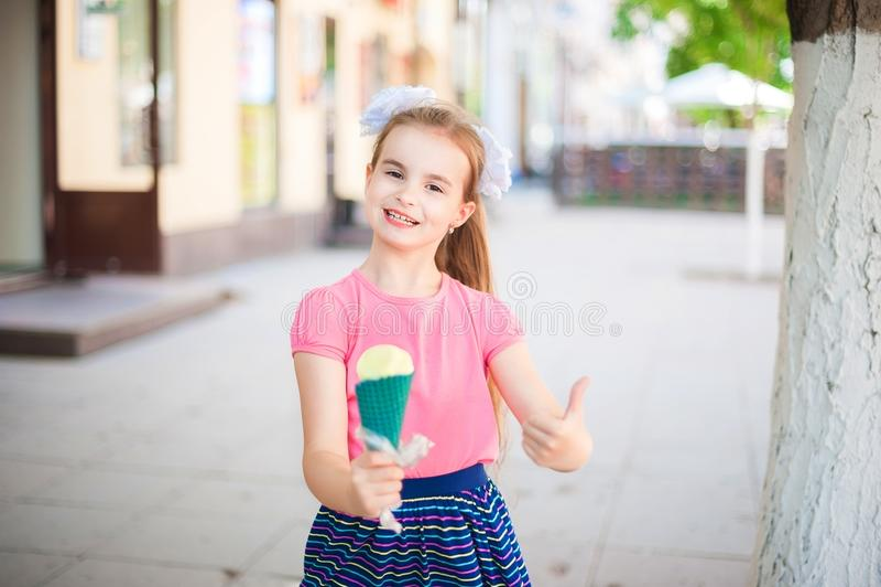 Una muchacha en una camiseta rosada y una falda multicolora brillante está sosteniendo el helado en un cuerno verde El helado y l fotos de archivo libres de regalías