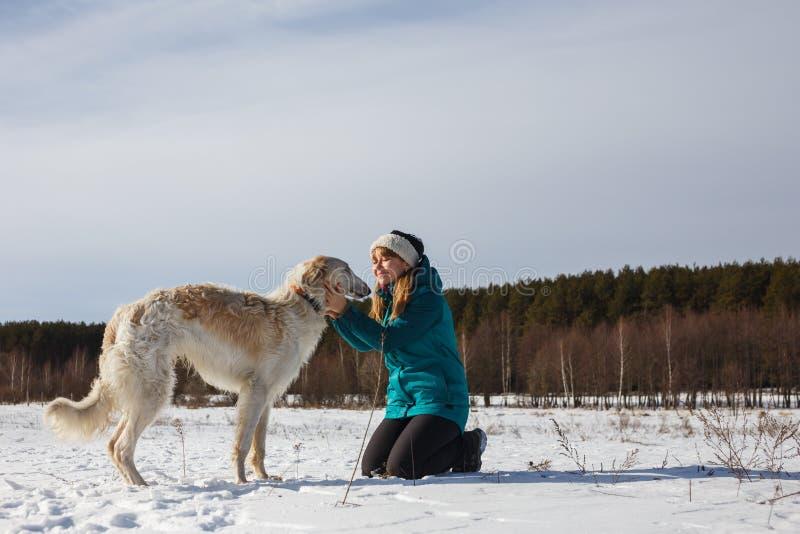 Una muchacha en una chaqueta de esquí verde en sus rodillas y un perro blanco ruso en un campo nevoso en invierno soleado imágenes de archivo libres de regalías